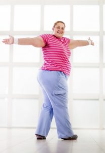 Smiling overweight woman having a sports training and looking at camera.